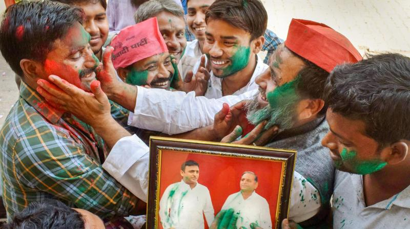 Samajwadi Party supporters apply 'gulal' on a photo of SP chief Akhilesh Yadav and party founder Mulayam Singh Yadav as they celebrate their lead in Phulpur and Gorakhpur Lok Sabha by-poll election, in Allahabad. (Photo: PTI)