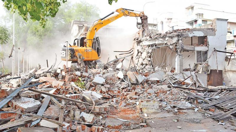 An earthmover pulls down a heritage building of the City Club at Tiruchy on Saturday. (Photo - DC)