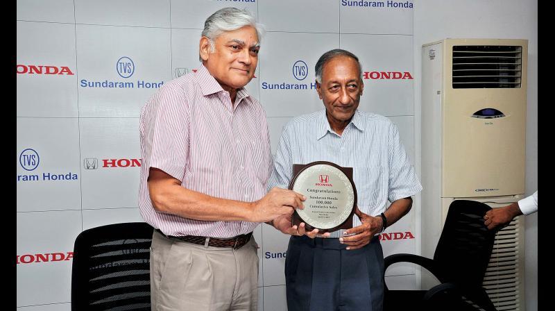 Executive director Sharath Vijayaraghavan of Sundaram Motors sharing the joy of the 'one-lakh cumulative customers' with joint managing director Ram Santhanam  of TVS & Sons.