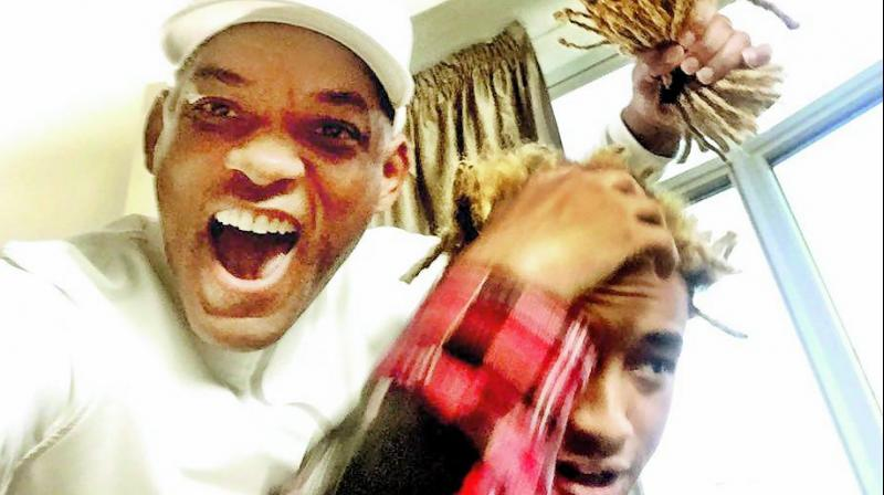 Will Smith poses with Jaden's dreads that he chopped off.