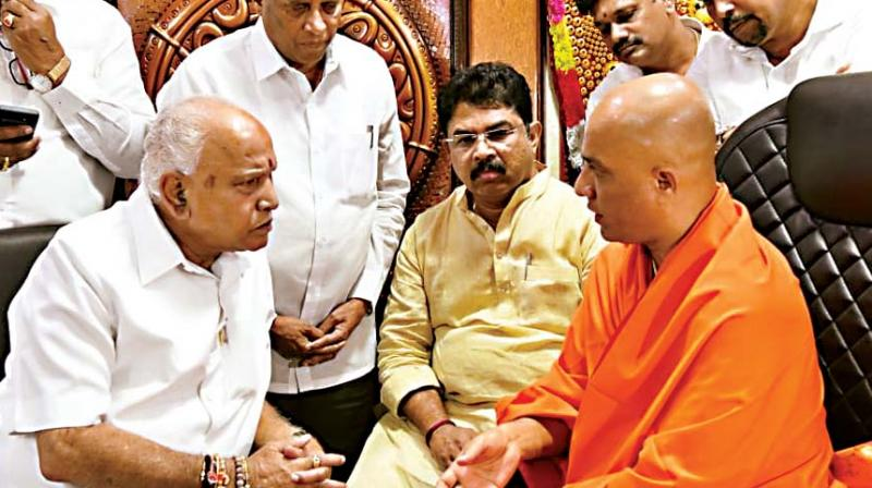 Chief Minister B.S. Yediyurappa and his cabinet colleagues with Sri Nirmalanadanatha Swamy in Bengaluru Wednesday (Photo: DC)