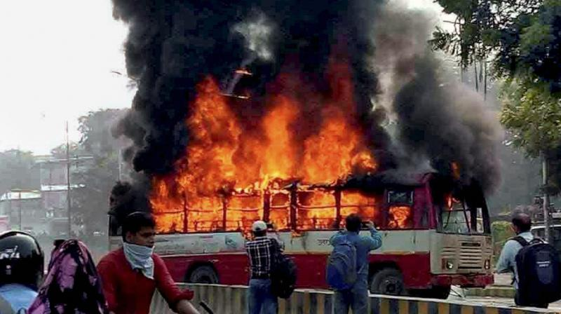 Angry mob set a bus on fire after Bahujan Samaj Party (BSP) leader Rajesh Yadav was shot dead outside an Allahabad University hostel. (Photo: PTI)