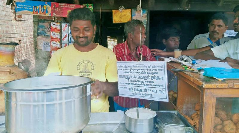 Sivakumar at his tea shop in Vamban village near Pudukkottai with the announcement board on the loan write-off to his left. (Photo: DC)