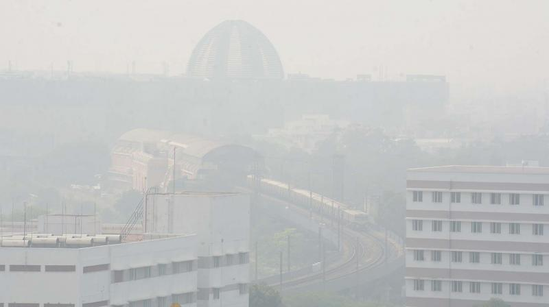 On a heavily hazy Friday around 11.30 am, a local train found coming from the Central railway station. Omandurar government multi super speciality hospital can be seen in the background. (Photo: DC)