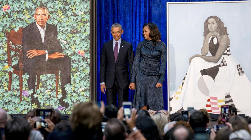 Former President Barack Obama and former first lady Michelle Obama stand on stage as their official portraits are unveiled at a ceremony at the Smithsonian's National Portrait Gallery, Monday, Feb. 12, 2018, in Washington. (Photo: AP)