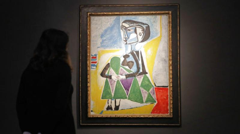 A Christie's auction house staff member poses for photographs in front of the 1954 Pablo Picasso painting