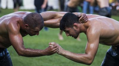 Massive men walk around the lawn turned into a wrestling ring to the tune of traditional music, their torsos slathered in olive oil, for an annual festival that blends the traditions of ancient Greece and more modern times. (Photo: AP)