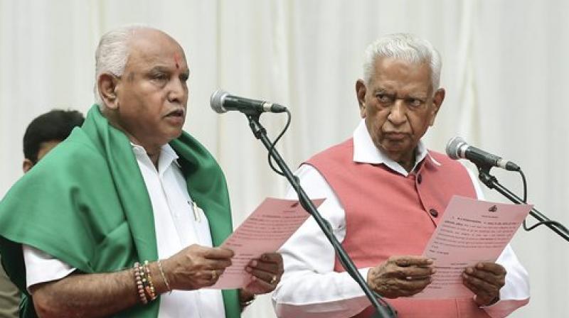Karnataka Governor Vajubhai Vala administers oath to Bharatiya Janata Party (BJP) leader B. S. Yeddyurappa as Chief Minister of the state at a ceremony in Bengaluru on Thursday. (Photo: PTI)