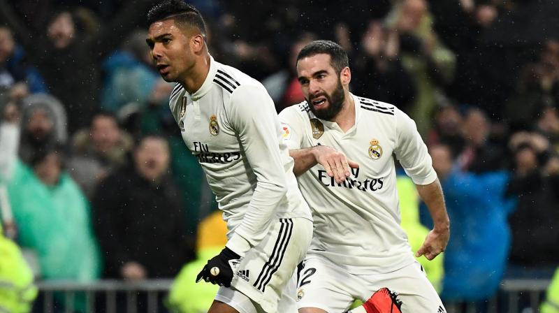 Casemiro celebrates with Dani Carvajal after scoring a goal during the match between Real Madrid and Sevilla. (Photo: AFP)