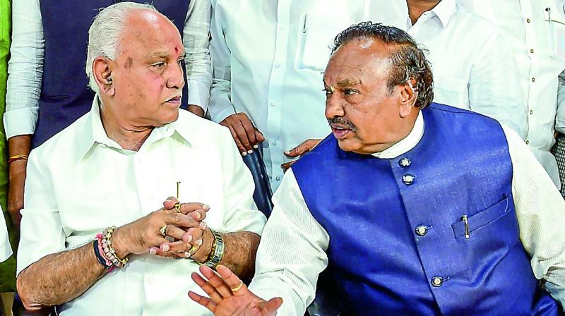 Karnataka BJP president B.S. Yeduyurappa with party leader K.S. Eshwarappa during a meeting of the BJP Legislature Party in Bengaluru on Monday.  (PTI)