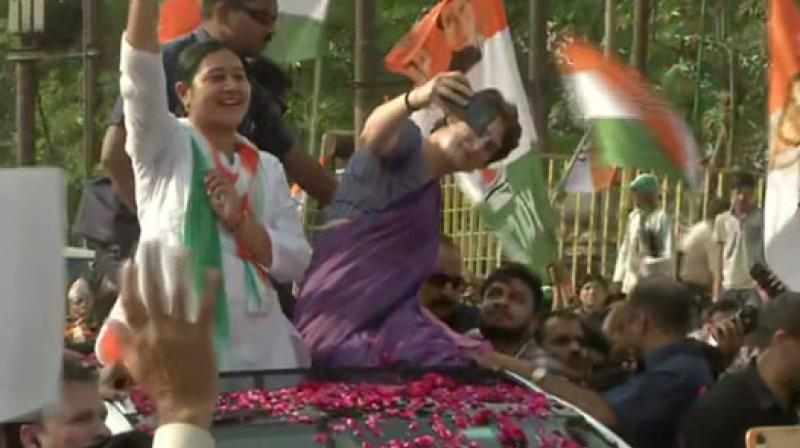 Priyanka Gandhi kept taking mobile phones of the supporters whoever requested for selfie and obliged them. (Image: ANI)