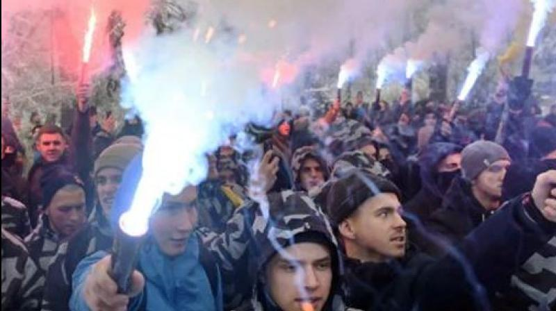 Activists hold flares during their rally in front of the Ukrainian parliament. (Photo: AFP)