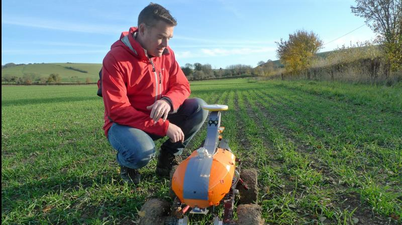 "Joe Allnutt, lead roboticist at British startup company the Small Robot Company, inspects a farming robot named Tom as part of a trial in East Meon, southern England, Friday Nov. 30, 2018. The ""agri-tech"" startup company is developing lightweight autonomous machines that can carry out precision ""seeding, feeding and weeding"" in the hope of transforming food production. (AP Photo / Kelvin Chan)"