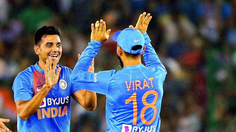 Deepak Chahar (left) celebrates taking a South African wicket with captain Virat Kohli during the second T20 international match in Mohali on Wednesday. (Photo: AP)