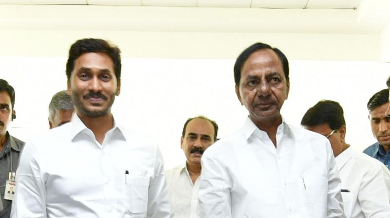 Andhra Pradesh Chief Minister Y.S. Jagan Mohan Reddy (left) and Telangana State Chief Minister K. Chandrasekhar Rao (right) step into the meeting venue Pragathi Bhavan in Hyderabad on Friday with their right foot as a mark of their resolve to solve the issues.  (DC)