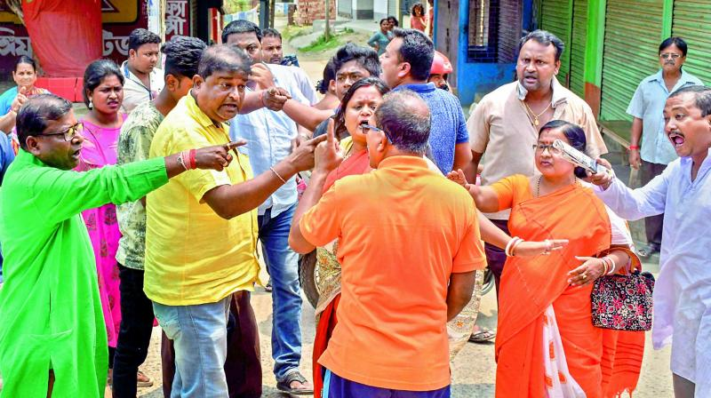 TMC and BJP workers quarrel outside a polling station, during the third phase of Lok Sabha elections, in Malda district of West Bengal on Tuesday. (Photo: AP)