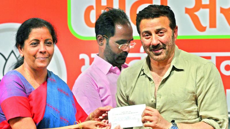 BJP leader Nirmala Sitharaman presents a membership slip to actor Sunny Deol as he joins the party in New Delhi on Tuesday. (Photo: Bunny Smith)