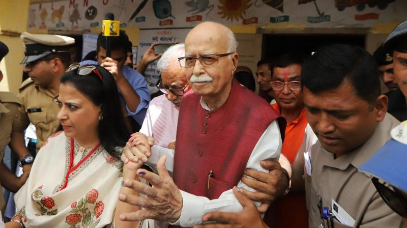 BJP veteran L.K. Advani leaves along with his daughter Pratibha after casting his vote at a polling booth in Ahmedabad on Tuesday. (Photo: AP)