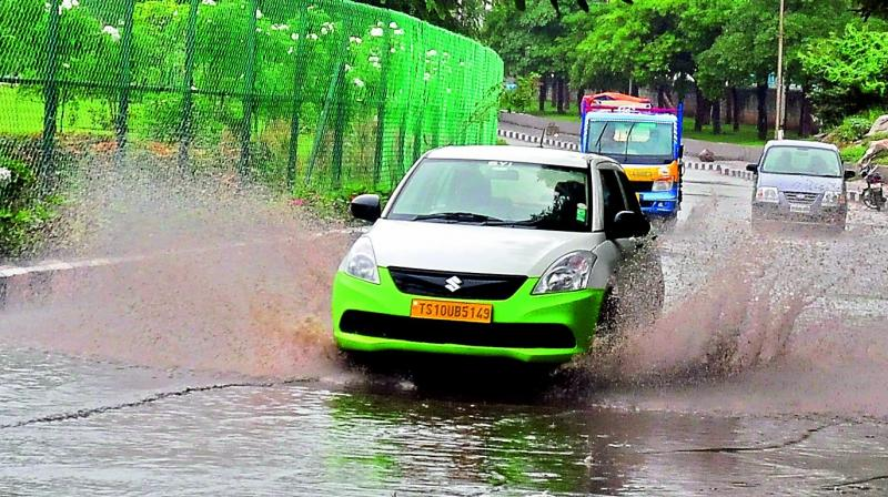 A car speeding through the stagnated rainwater in the Necklace road on Friday evening.  (Photo: P. Surendra)