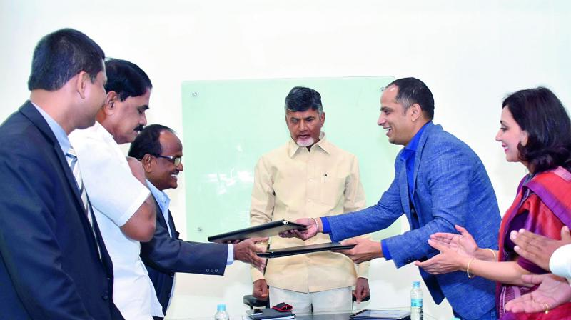 Officials of the Government of AP and Monetary Authority of Singapore sign an MoU on Fintech  in the presence of Chief Minister N. Chandrababu Naidu at his house in Vijayawada on Saturday. (Photo: DC)