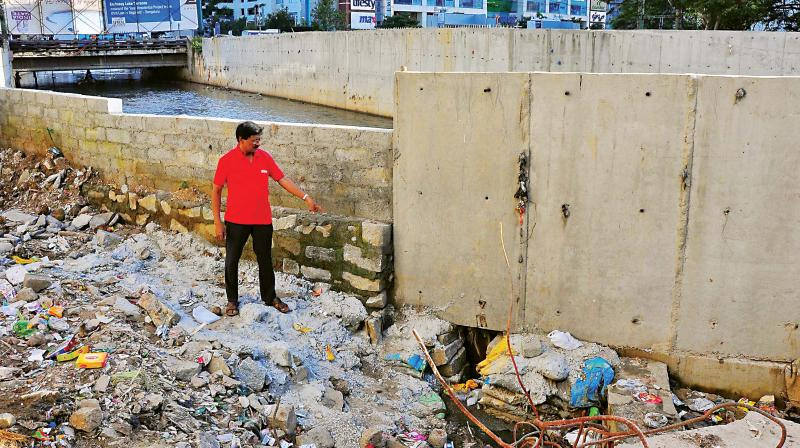 Anil from Ashwini Layout shows the broken wall of the major drain in Koramangala 	(Photo:Satish B)