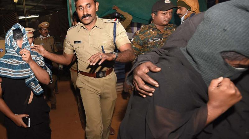 Reshma Nishanth and Shanila Rajesh being escorted by cops to the vehicle outside the police control room in Nilakkal on Saturday.