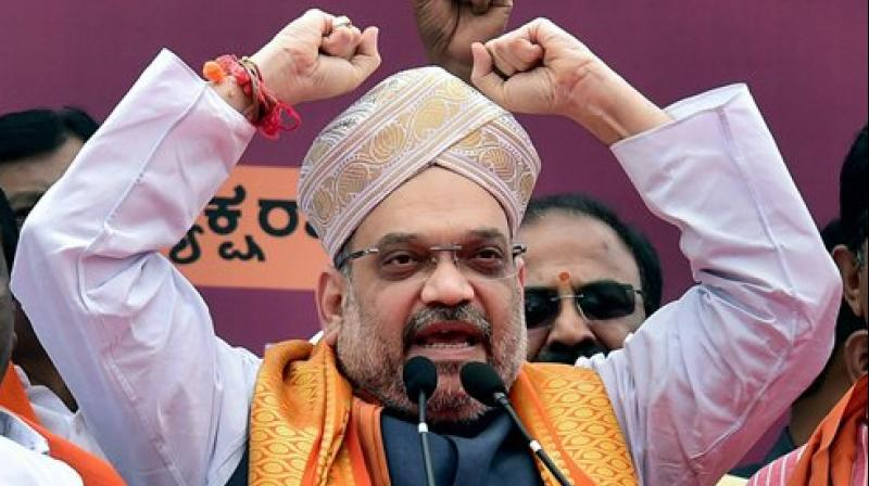 BJP president Amit Shah wears a Mysore Peta, a traditional headgear, upon his arrival on a three-day visit to Karnataka as part of his 110-day nationwide tour, in Bengaluru on Saturday. (Photo: PTI)