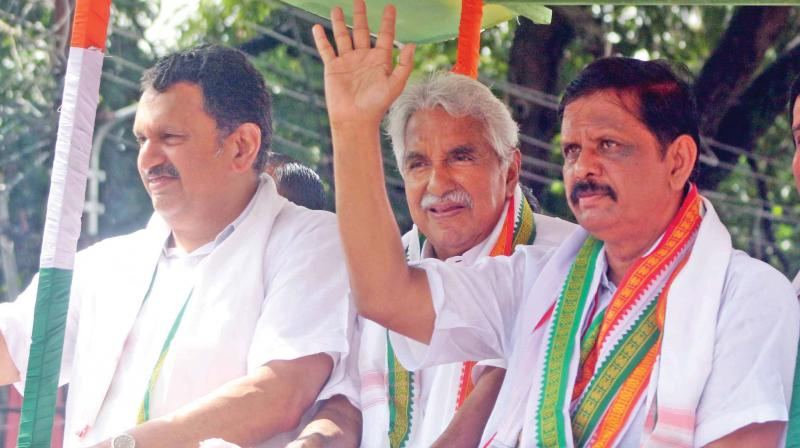 Congress leaders K. Muraleedharan and Oommen Chandy along with UDF candidate K. Mohankumar atop campaign vehicle during electioneering in Vattiyoorkavu constituency on Thursday. (Photo: A.V. MUZAFAR)