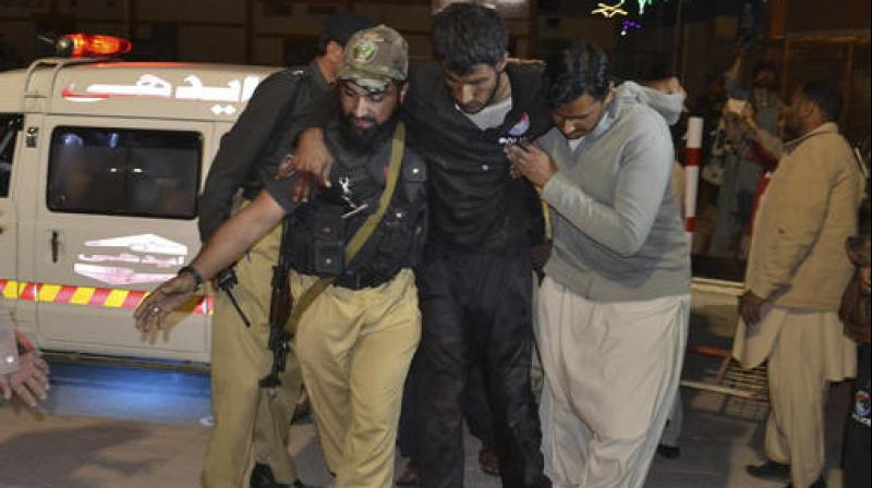 A Pakistani volunteer and a police officer rush an injured person to a hospital in Quetta, Pakistan. (Photo: AP)