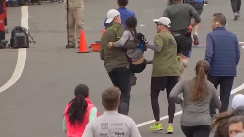 In the clip, the woman is seen trying hard to keep up with other marathon participants before being helped by three men who stop mid-race for her. (Credit: YouTube)