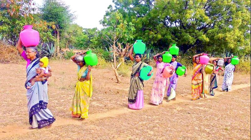 Women getting water from borewell.