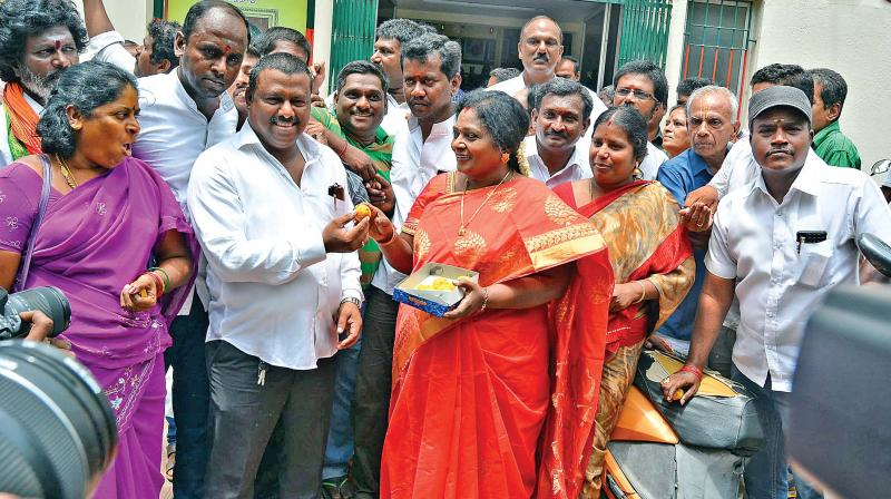 State BJP president Tamilisai Soundararajan distributes sweets at her office on Tuesday following victory in Karnataka elections