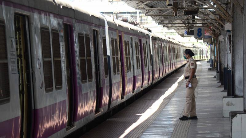 A police officer stands on the empty platform in Kurla station in Mumbai after local train services were opened from COVID-19 frontline staff