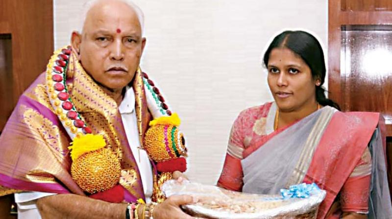 Mayor Gangambike with the dry fruits packet covered in plastic that she presented to B.S. Yediyurappa