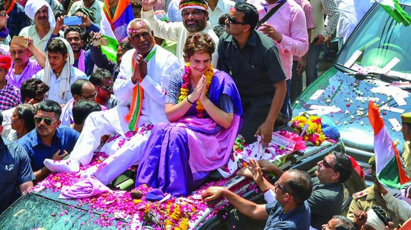 Congress general secretary Priyanka Gandhi Vadra greets supporters during an election campaign rally in support of the party candidate Shiv Sharan Kushwaha (to Priyanka's right) in Jhansi on Thursday.  (PTI)