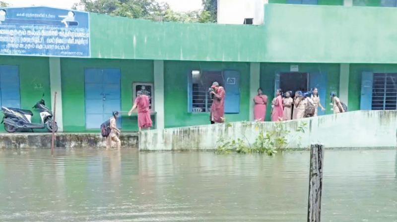 Students wade throughr knee-deep water to enter the classrooms in Kancheepuram high school.