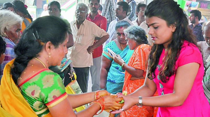 A woman gives prasadam to a girl at Mulastaneswara Swamy temple in Nellore on Monday. (Photo:  DC)