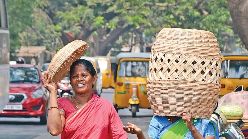 Two women cover themselves using bamboo baskets to escape heat at Chetpet. (Photo: DC)