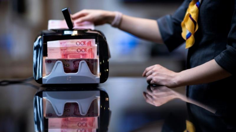 The People's Bank of China on Wednesday fixed the yuan's central parity rate at 6.9996 per US dollar. (Photo: AFP)
