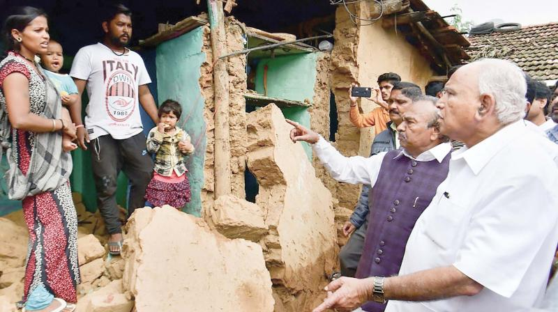 Chief Minister B.S. Yediyurappa speaks to family members whose house was damaged in rain a few days ago in Shivamogga on Tuesday  (Photo:PTI)