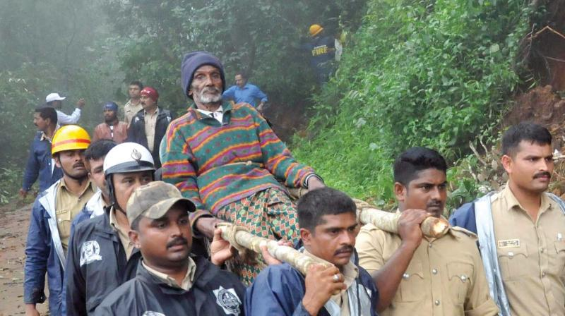 Fire Brigade personnel carry a flood victim to safety at Allekhan near Mudigere on Tuesday.  – KPN