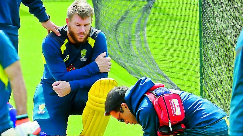 Australia's David Warner (left) looks on as an injured net bowler receives medical attention during a training session at The Oval in London on Saturday.	(Photo: AFP)