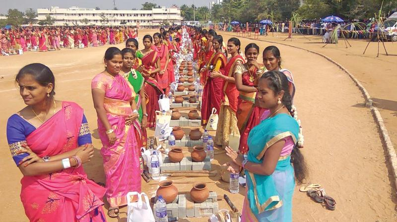 Woman students line up with earthen pots to make sweet Pongal on the college campus on Friday. (DC)