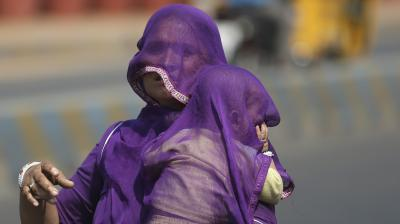 A mother and child cover their heads from the sun as they await the start of the monsoon season. (Photo: AP)