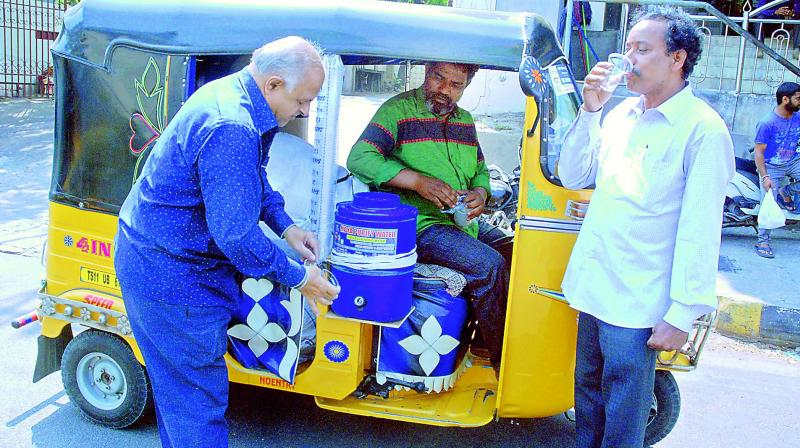 Auto driver, Shaik Saleem with a water cooler attached to his auto.    (Style Photo service)