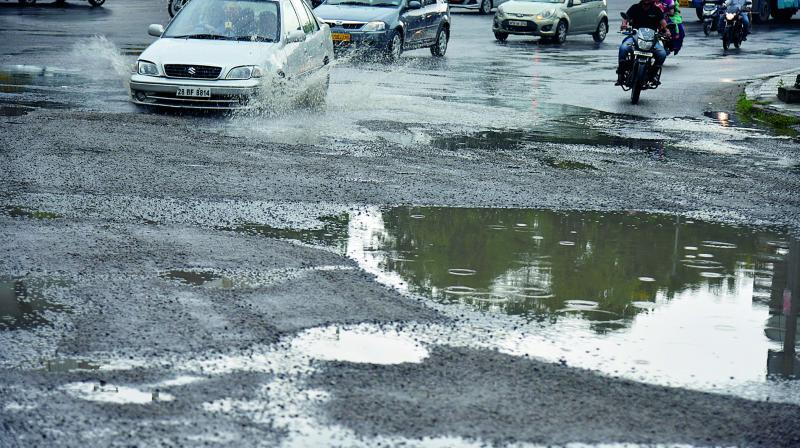 Motorists find it hard to negotiate on roads damaged by heavy rains, adding to the existing chaotic traffic in the city. (Photo: DC)