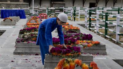 A Kashmiri boy lays a wreath on a grave at Martyr's Graveyard in Srinagar, Kashmir on Saturday. (Photo: AP)
