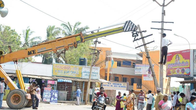 Tamil Nadu electricity board workers install a new electrical post at Karuku on Monday (Photo: DC)