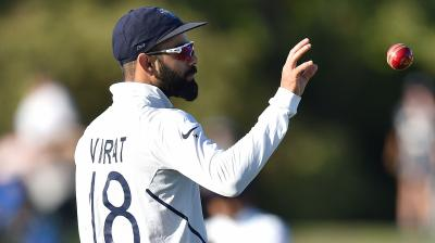 Indian captain Virat Kohli catches a ball on day one of the second Test cricket match between New Zealand and India (AFP)