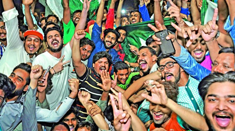 Pakistan fans celebrate their team's triumph over India in the final of the ICC Champions Trophy on Sunday (Photo: AP)